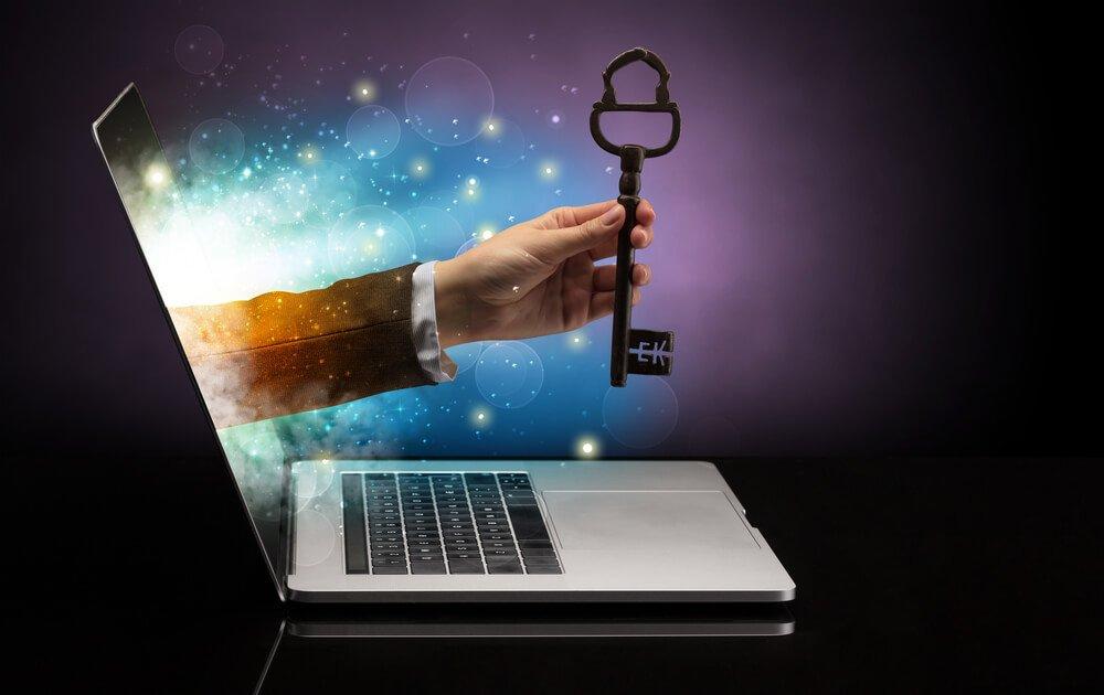Ein Schlüssel der von einer Hand aus dem Monitor gehalten wird. Der Schlüssel zum Glück mit Hilfe eines Glückscoach.