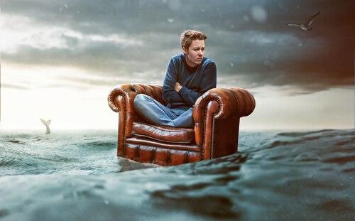 Mensch im Schneidersitz auf Ledersessel mitten im Ozean. Kann man so alleine glücklich sein?