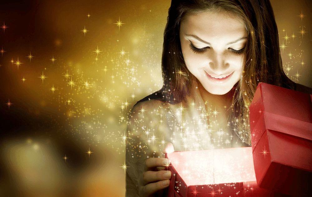 Mädchen fragt sich bin ich glücklich und schaut in eine funkelnde Geschenkbox