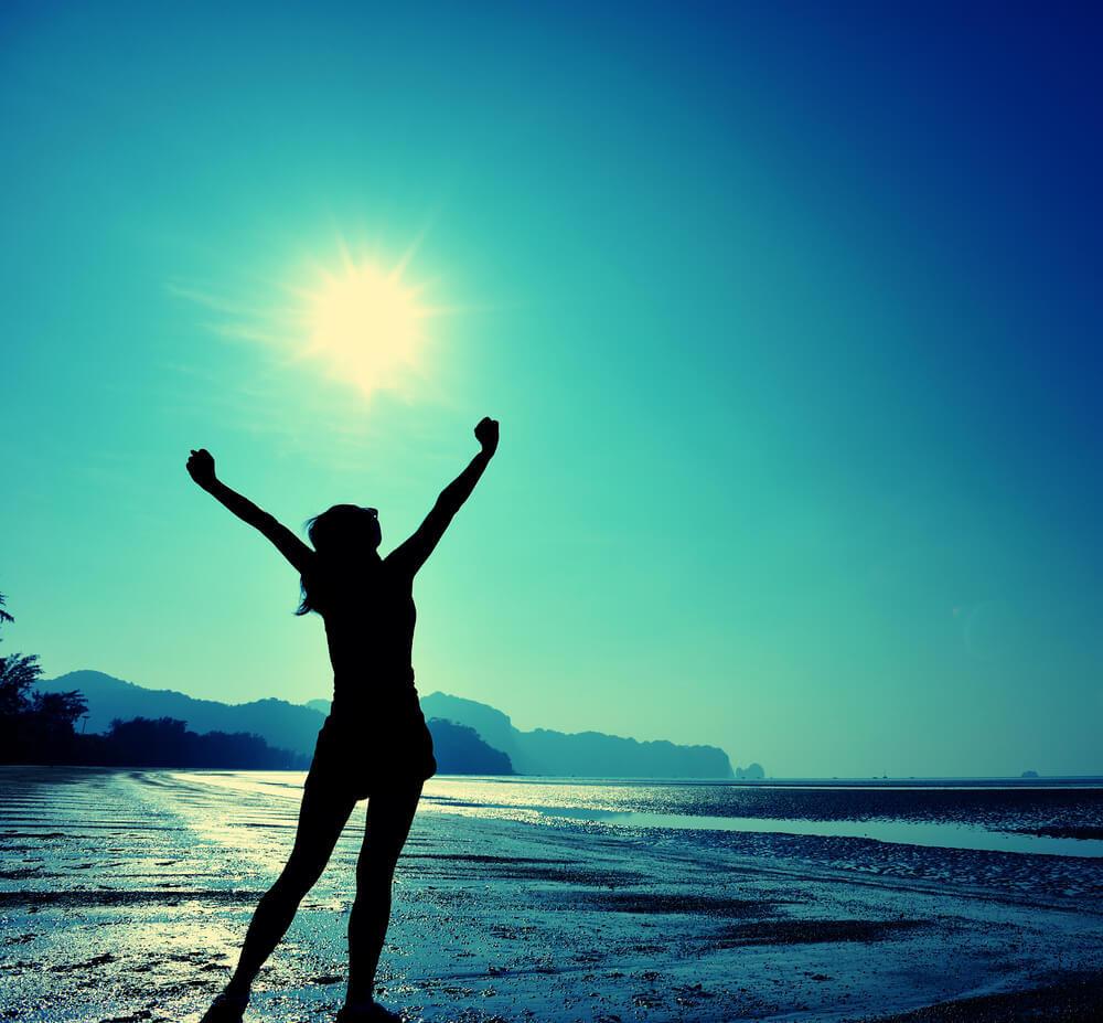 Frau am Meer streckt die Arme in die Luft. Will glücklich sein.