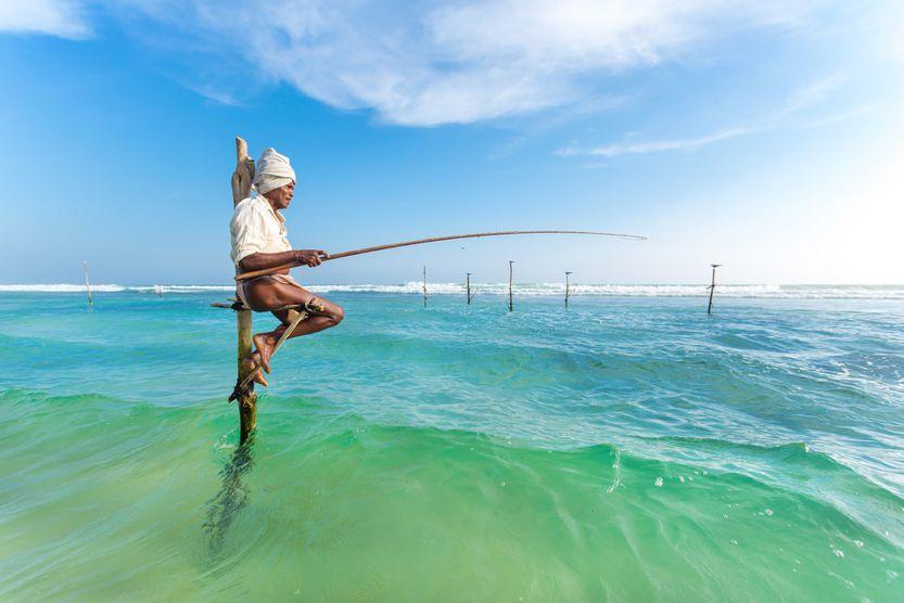 Mensch sitzt auf einem Pfahl im Meer und angelt. Was macht glücklich? 13 Dinge die glücklich machen erfährst du in diesem Beitrag.