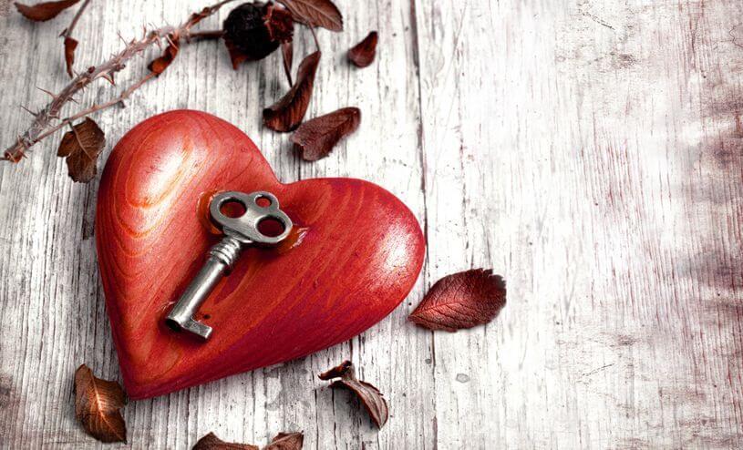 Glücklich machen mit dem richtigen Schlüssel, der auf einem Herz liegt.