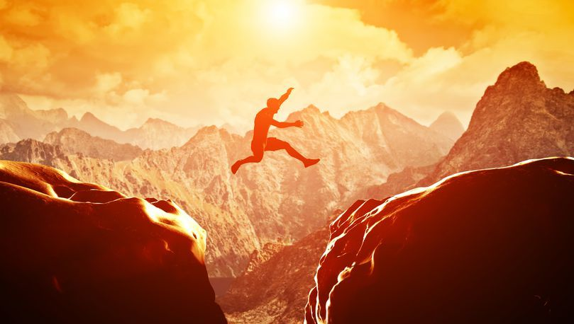 Man springt über Klippe und ist glücklich und zufrieden das er sich zum Sprung entschieden hat.