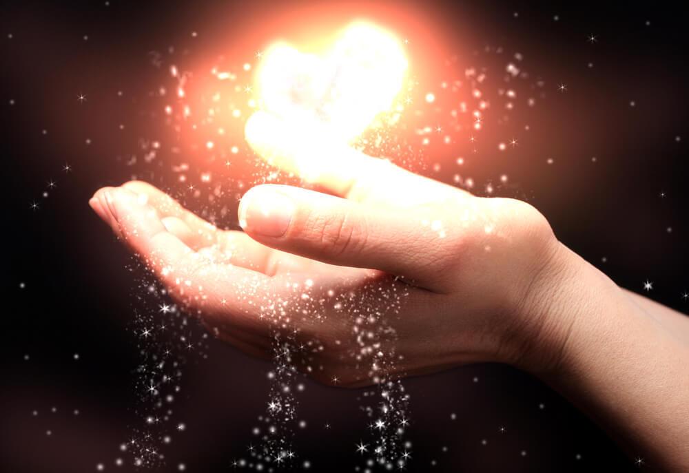 2 offen gehaltene Hände. Über ihnen schwebend ein leuchtender runder Gegenstand. Symbolisiert Glück finden