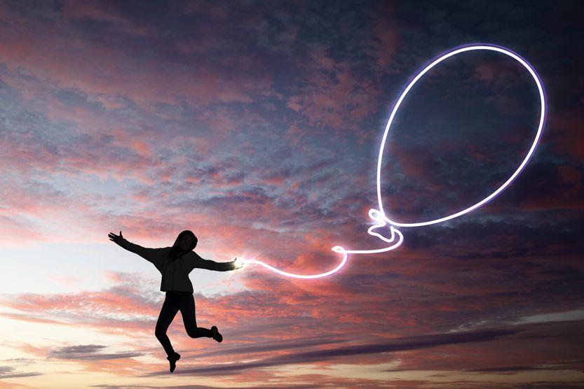 Glück im Leben hat diese junge Frau die mit einem gezeichneten Ballon in die Höhe steigt.