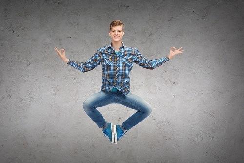 lachender junger Mann im Schneidersitz will glücklich werden