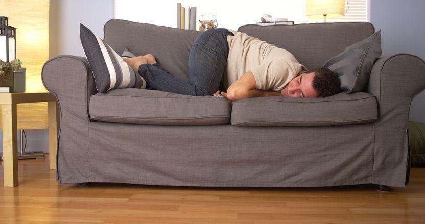 Man mit Schlafstörungen liegt auf einer Couch