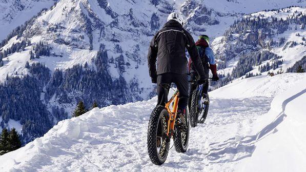 Fahrrad fahren auf dem verschneiten Berg macht glücklich